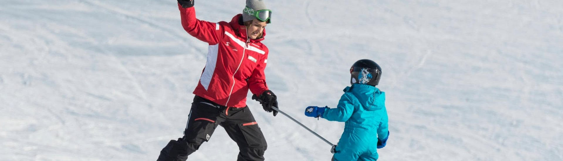 A ski instructor fom Skischule Schwarzenberg am Bödele is practicing some basic skiing techniques with a young child during their private ski lessons for kids from 3.5 y.