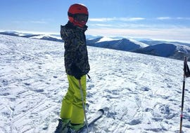 A skier is standing at the top of a slope waiting to start their Private Ski Lessons for Kids - Holidays with the ski school Moonshot La Bresse.