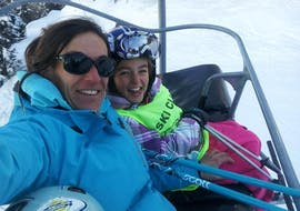 A kid is sitting on a chairlift next to their ski instructor from the ski school ESI Ecoloski Barèges during their Private Ski Lessons for Kids - Low Season.