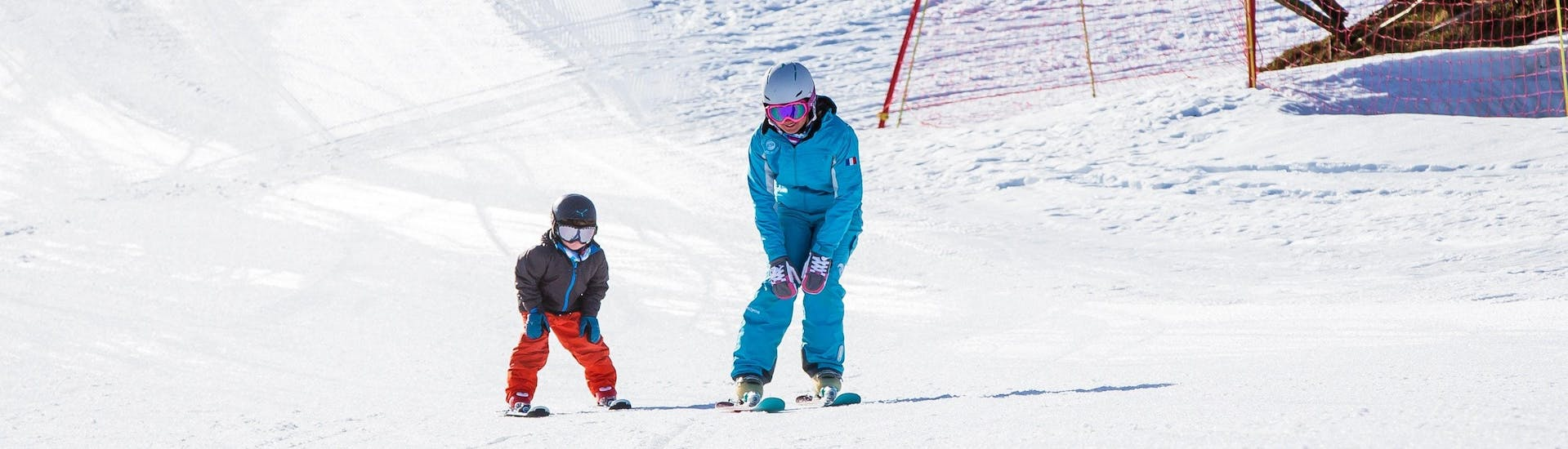 A ski instructor from the ski school ESI Ski Family in Risoul is skiing alongside a child during their Private Ski Lessons for Kids of All Levels - Morning.