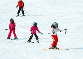 During the Private Ski Lessons for Kids of All Ages with Hansis Skischule Steinach am Brenner, three children are practicing their skiing skills with the help of an experienced instructor.