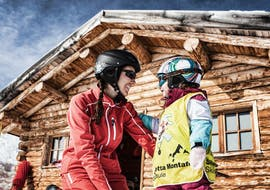 A ski instructor is helping a little kid with their first skiing experience during the Private Ski Lessons for Kids of All Ages with Skischule Schruns.