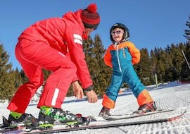 A ski instructor from the ski school ESF La Foux d'Allous is teaching a young child how to ski during their Private Ski Lessons for Kids of All Levels.
