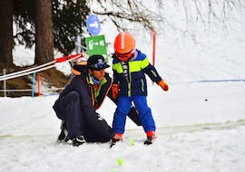 A ski instructor from the ski school Evolution 2 La Plagne Montchavin - Les Coches is helping a young skier finding his balance during his Private Ski Lessons for Kids of All Levels.