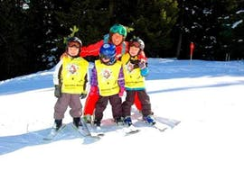 A group of friends together with a ski instructor from the Ski School St.Gallenkirch learn the basic techniques on the piste during the Private Ski Lessons for Kids of All Levels.