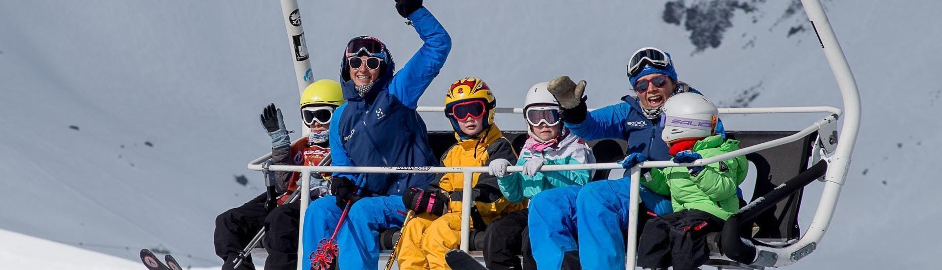 A group of children is riding the chair lift together with their ski instructors from the ski school Ski Cool during their Private Ski Lessons for Kids - School Holiday - Morning in the ski resort of Val Thorens.