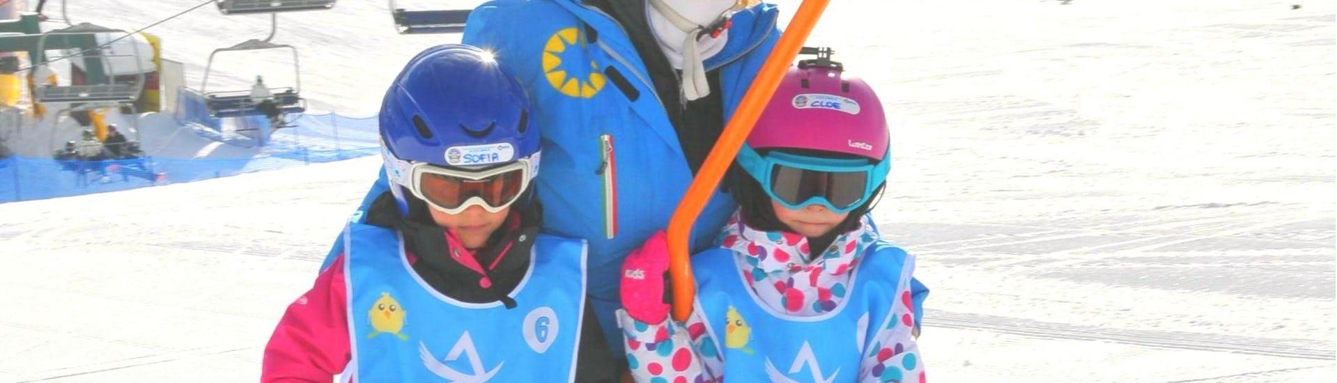 A ski instructor shows the use of the ski lift to two children during the  Private Ski Lessons for Kids - All Levels of the ski school Scuola di Sci Azzurra Livigno.