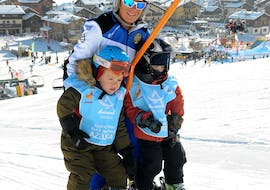 A ski instructor of Scuola di sci Azzurra Livigno on the skilift on with two kids during the Private Ski Lessons for Kids of All Levels in Livigno.