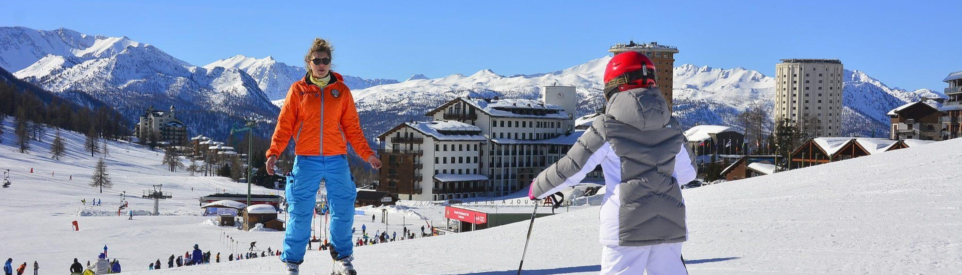A young skier is skiing towards his ski instructor from the ski school YES Academy Sestriere during his Private Ski Lessons for Kids - Special - All Levels.