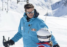 A young skier is receiving precious advice from their ski instructor from the 333 ski school in Tignes before their Private Ski Lessons for Kids - Tignes.