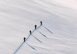 A group of skiers is hiking up the snowy mountain alongside Skischule Private Lech's Private Ski & Splitboard Touring Guide for All Levels.