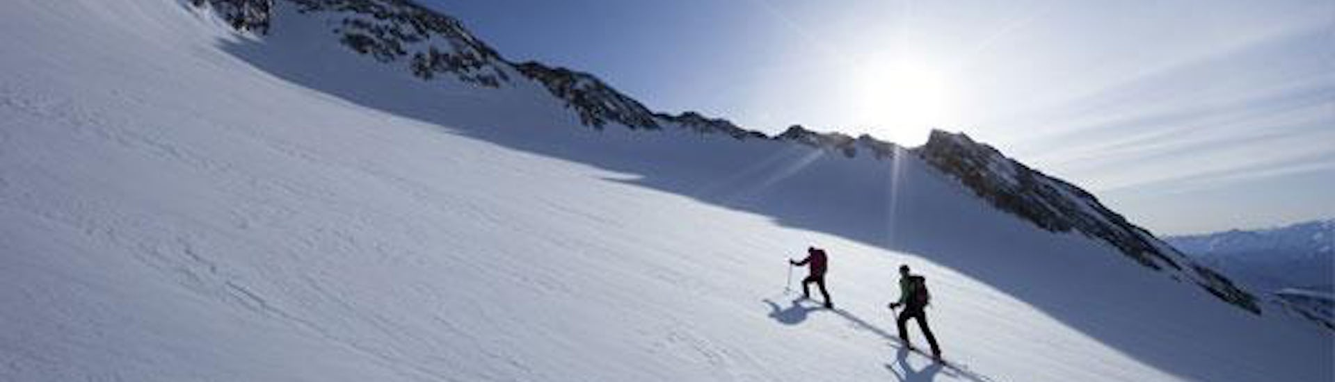 Two participants of the Private Ski Touring Guide - Difficult organized by the school Alpinschule Sölden are skiing on a snowy landscape in the ski resort of Sölden.