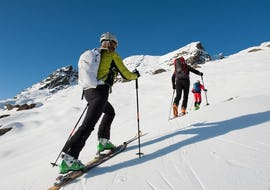 Skiers climbing a slope during their Private Ski Touring Guide for Adults - Beginner with the ski school ESI Valfréjus.