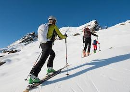 Des skieurs gravissent une pente pendant leur Ski de randonnée privé pour Adultes - Débutant avec l'école de ski ESI Valfréjus.