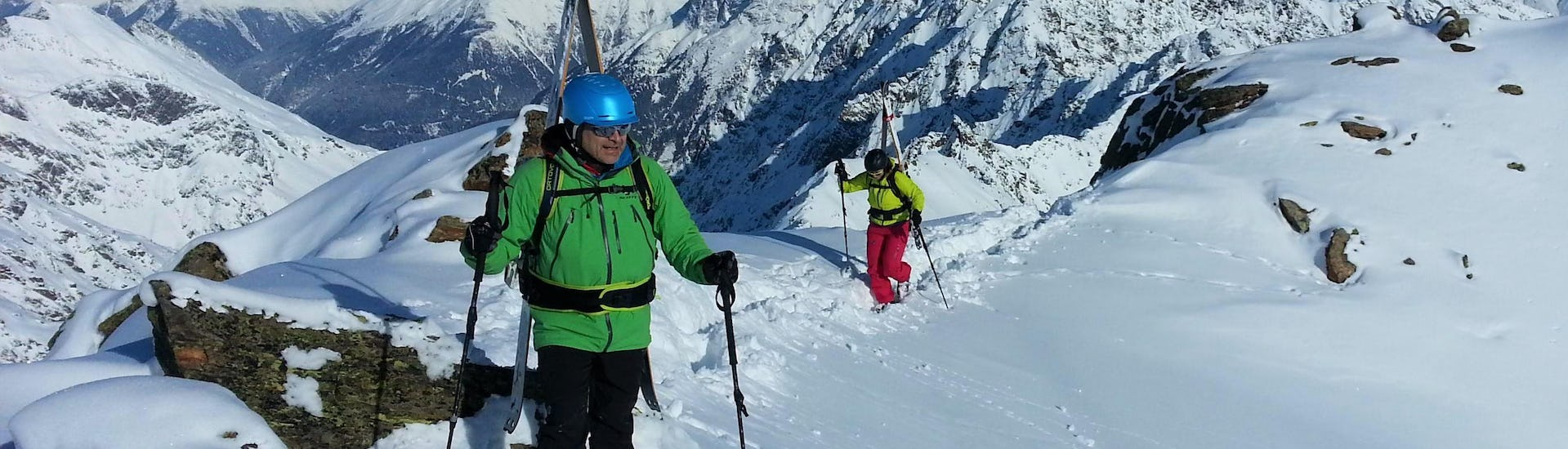 A private ski touring guide from the ski school Ski- und Snowboardschule SNOWLINES Sölden is showing the magnificent view of the snowy peaks of the ski resort of Sölden to a participant of the Private Ski Touring Guide.