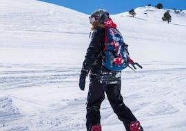 Un snowboarder baja por la pista mientras observa la montaña durante las Clases particulares de snowboard - Todas las edades  de la Escuela Ski Sierra Nevada.