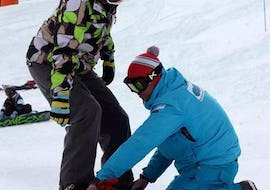 An instructor from the snowboarding school Cab9 Snowboarding is helping a young man to fix the snowboard during Private Snowboarding Lessons for All Ages and All Levels.