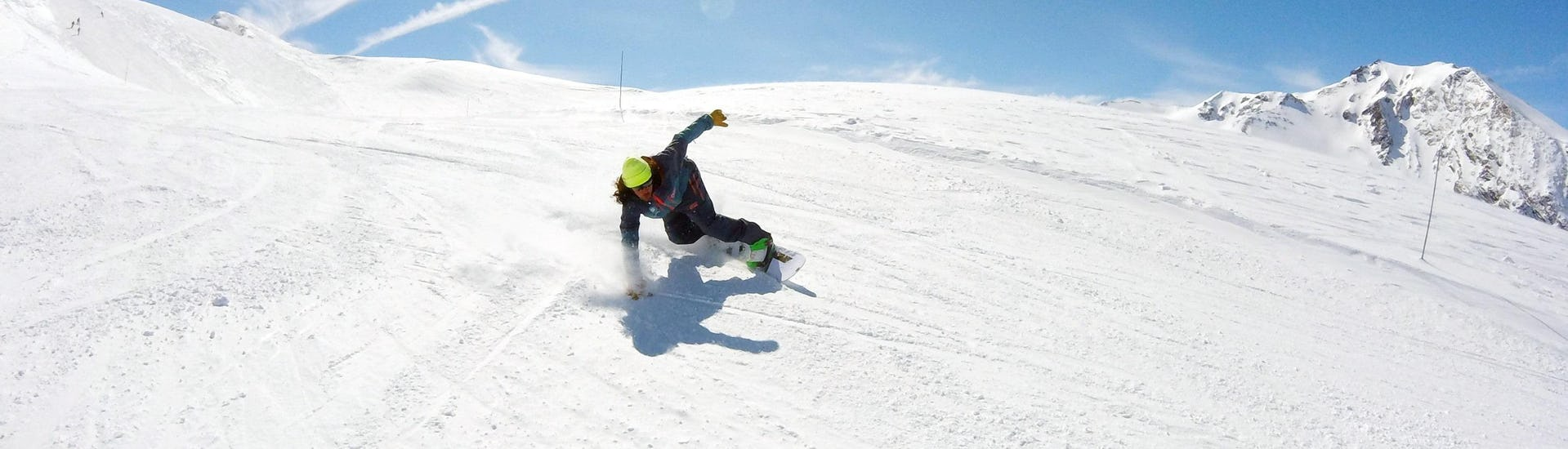 A snowboarder is sliding down a snowy slope during his Private Snowboarding Lessons - All Levels & Ages with the ski school ESI Valfréjus.