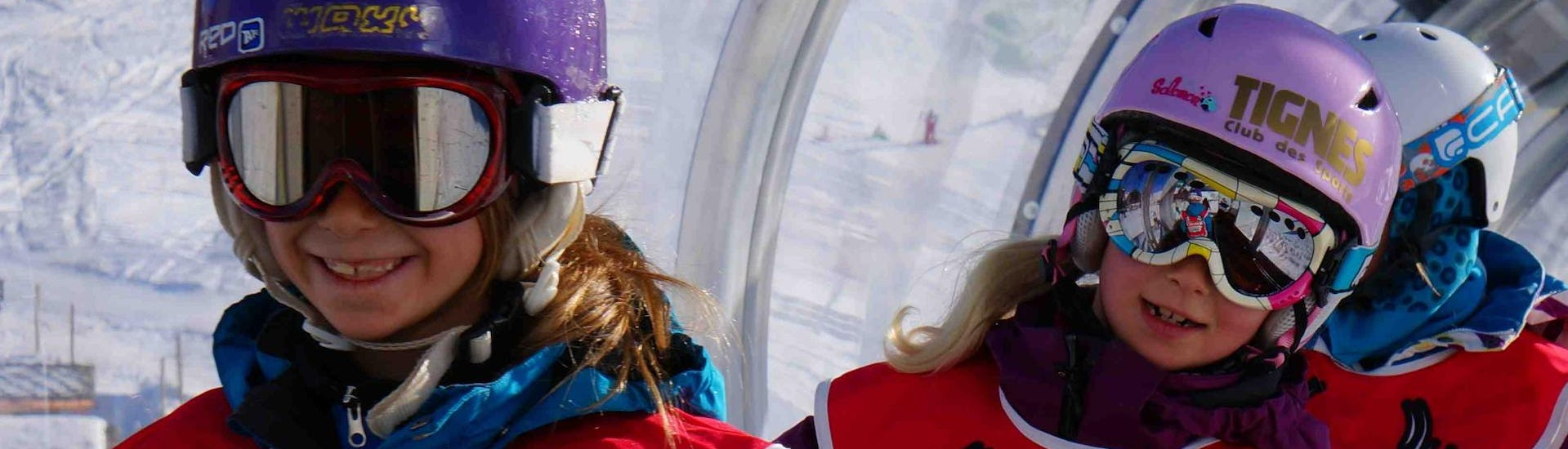Two young children are enjoying their first session of Private Snowboarding Lessons - All Levels & Ages in the ski resort Val d'Isère.