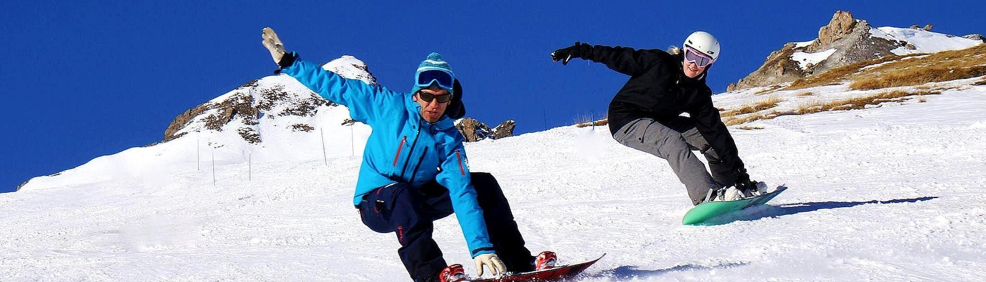 A snowboarder is following their instructor from the ski school Sncool in Tignes on a snowy slope while grabbing their board during theirPrivate Snowboarding Lessons - All Levels & Ages.