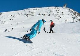 Un snowboardeur suit son moniteur de snowboard de l'école de ski ESI Dévoluy pendant son Cours particulier de snowboard.