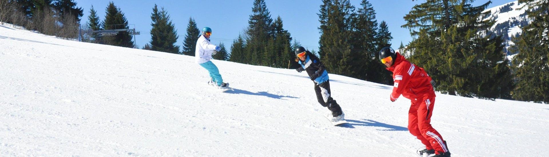Les snowboardeurs suivent leur moniteur de snowboard sur la piste pendant leur Cours particulier de snowboard pour Tous niveaux avec l'école de ski ESS Château d'Oex.