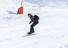 A man is improving his snowboard skills during the private snowboarding lessons for kids & adults - all levels in the Schneesportschule Thoma.