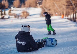 A little snowboarder is having fun during the Private Snowboarding Lessons for Kids & Adults - All Levels and benefits from the full attention of an instructor from the school Scuola di Sci B.foxes.