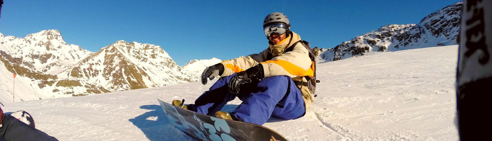 A snowboarder sits relaxed in the snow and enjoys the beautiful view during thePrivate Snowboarding Lessons for Kids & Adults of all Levels of Life Ski Escuela de Esquí Baqueira.