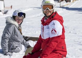 A child has lot of fun in the snow  with its private snowboarding instructor during a private snowboard lesson for kids and adults of all levels in Riezlern.