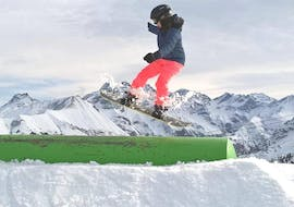 A child is enjoying the Private Snowboarding Lessons for Kids & Adults  - All Levels while trying some freestyle tricks under the supervision of an instructor from Alpin Skischule Oberstdorf.