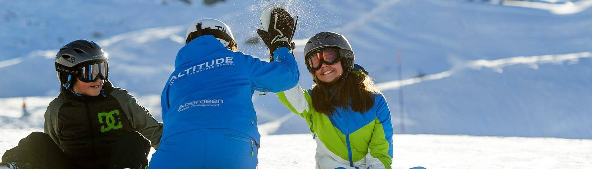 A snowboard instructor is high-fiving her student during the Private Snowboarding Lessons for Kids & Adults - All Levels with Altitude Ski School Zermatt.