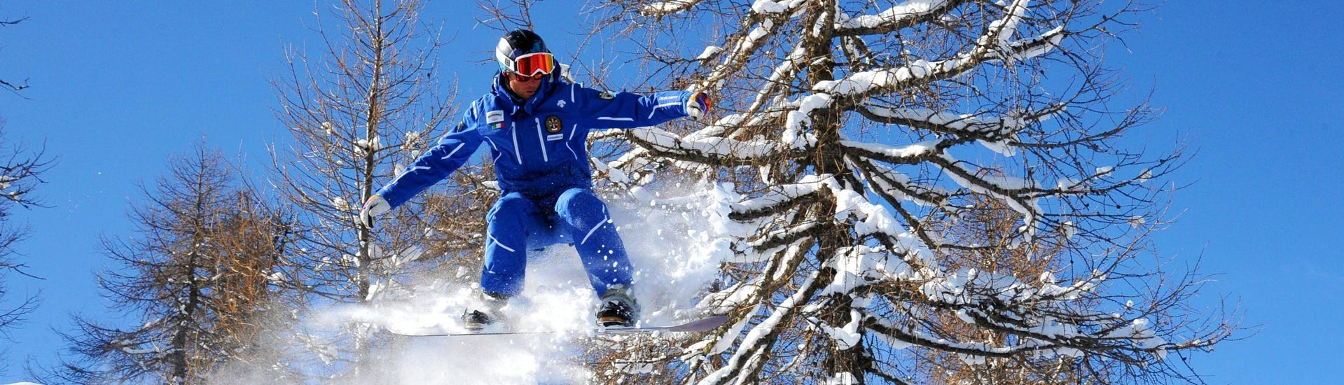 Private Snowboarding Lessons for Kids & Adults - All Levels of the Folgarida Dimaro Ski School are taking place, the snowboard instructor shows the technique on the slopes of Val di Sole.
