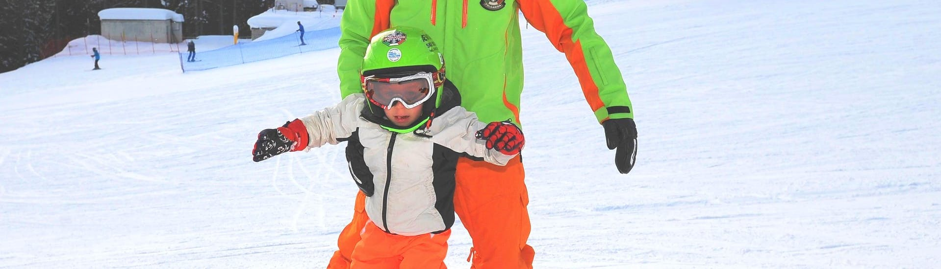 The rivate Snowboarding Lessons for Kids & Adults - All Levels have just started and the snowboard instructor of the Ski School Scuola di Sci Aevolution Folgarida is helping a child to maintain his balance.