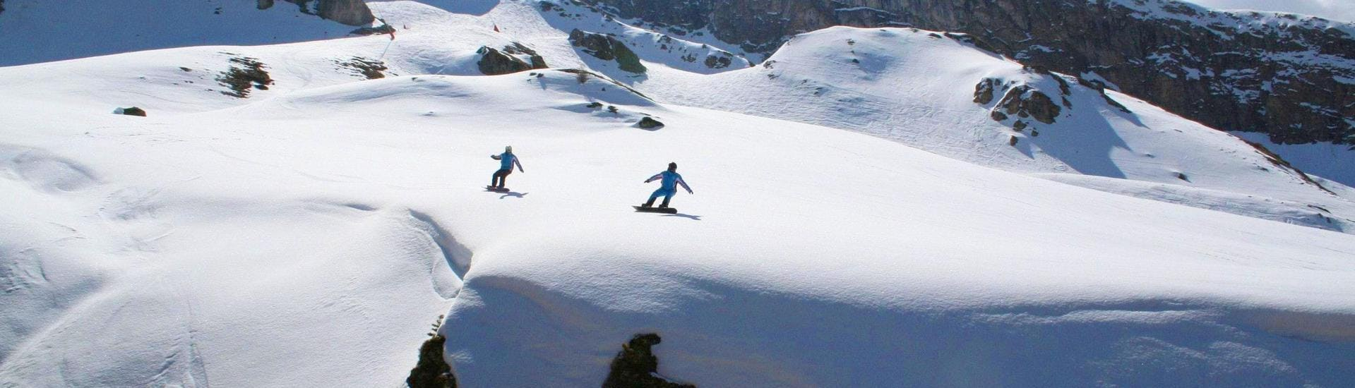A snowboarding instructor and a learner are gliding along an untouched powder snow slope during one of their Private Snowboarding Lessons for Kids & Adults - All Levels in the ski resort of Ischgl.