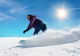 A snowboarder is sliding down a snowy slope during his Private Snowboarding Lessons for Kids & Adults - Low Season with the ski school ESI Easy2Ride Morzine.