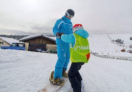 A snowboarder is learning how to keep their balance on the snowboard with their snowboard instructor from the ski school ESI Font Romeu during their Private Snowboarding Lessons for Kids & Adults - Low Season.