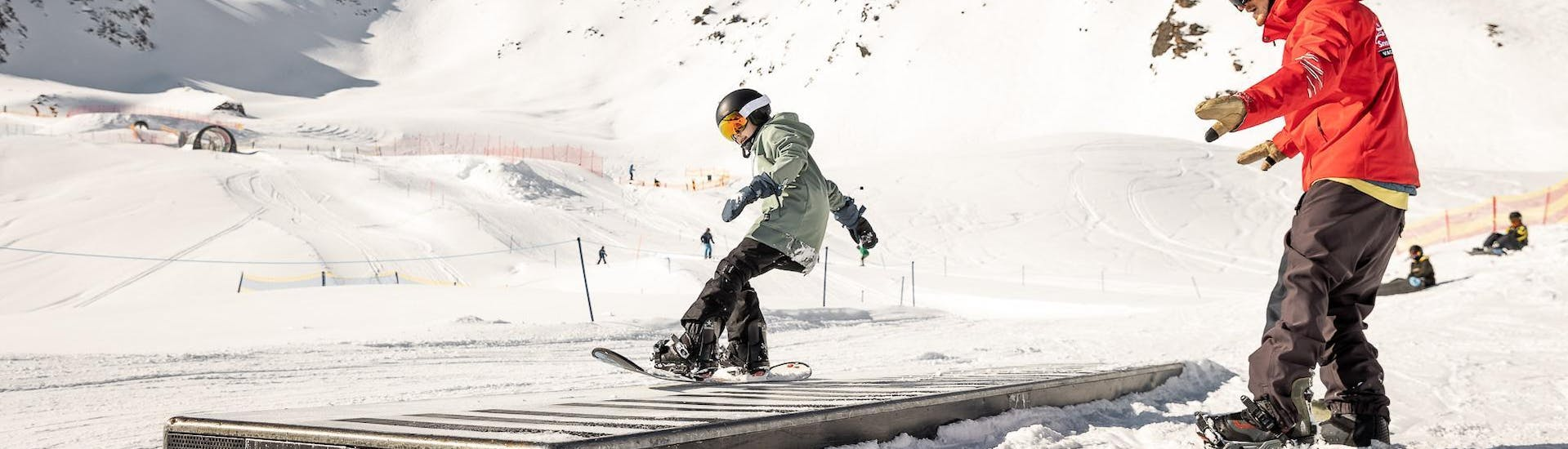 A young snowboarder is practicing new tricks during his Private Snowboarding Lessons for Kids - All Levels with the ski school Ski- und Snowboardschule Vacancia.