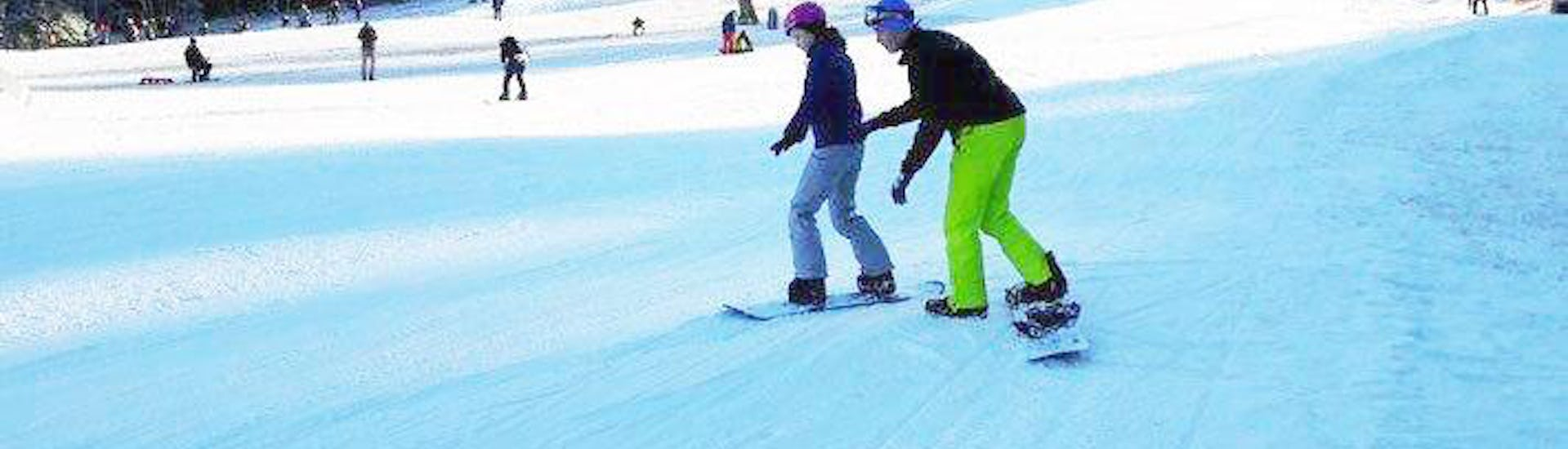 A young snowboarder is learning to snowboard during Private Snowboarding Lessons for Kids & Adults for All Levels with the ski school DSV Skischule Züschen.