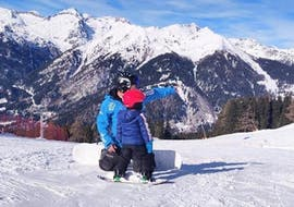 A private snowboard instructor is showing the slopes to a young snowboarder during the Private Snowboarding Lessons for Kids & Adults - All Levels organized by the ski school Scuola di Sci Pinzolo in the Val Rendena ski resort.