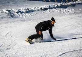 Un snowboardeur dévale une piste de poudreuse en confiance pendant son Cours particulier de snowboard pour Enfants & Adultes avec l'école de ski Evolution 2 Super Besse.