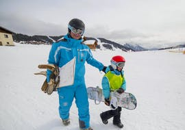 A snowboarder is walking besides their snowboard instructor from the ski school ESI Font Romeu at the bottom of the snowy slopes during their Private Snowboarding Lessons for Kids & Adults - Holiday.