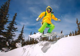 A snowboarder is descending a slope in the Via Lattea ski resort in Sestriere during a Private Snowboarding Lessons for Kids & Adults - Holidays offered by the school Scuola di Sci Olimpionica.