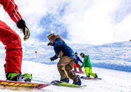 Three friends are exploring the slopes of the Silvretta Montafon ski resort alongside an experienced instructor during their Private Snowboarding Lessons for Kids & Adults of All Levels with Skischule Schruns.