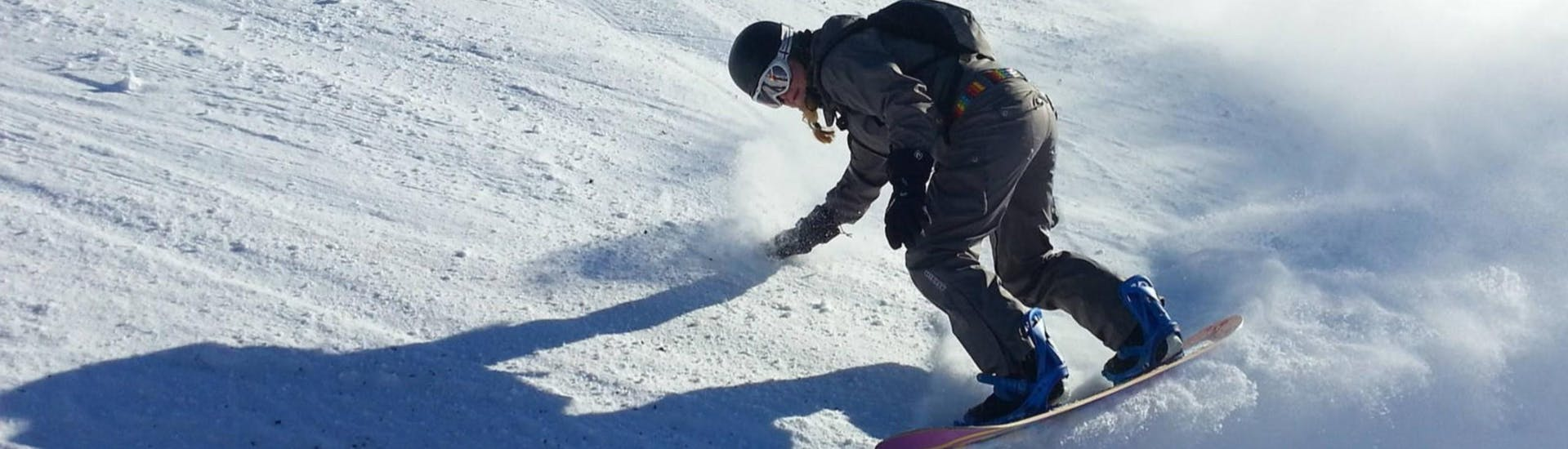 A young woman is practising her snowboarding skills during her private snowboarding lessons for kids and adults with Skischule Schwarzenberg am Bödele.