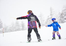 A snowboarder is paying attention to the snowboard instructor during the Private Snowboarding Lessons for Kids & Adults - All Levels organized bu the ski school YES Academy Sestriere.