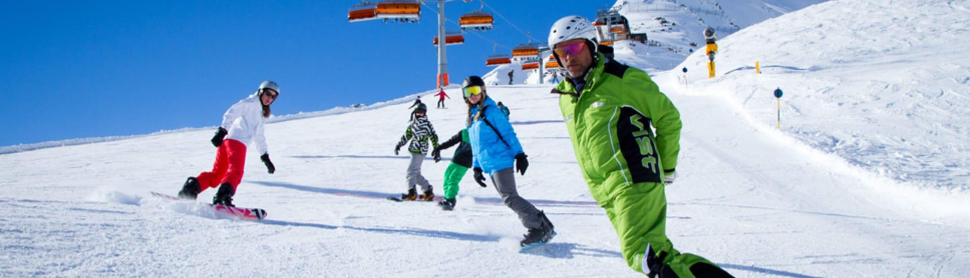 A group of people is learning to snowboard during their Private Snowboarding Lessons for Kids & Adults with the ski school Ski- und Bikeschule Ötztal Sölden.