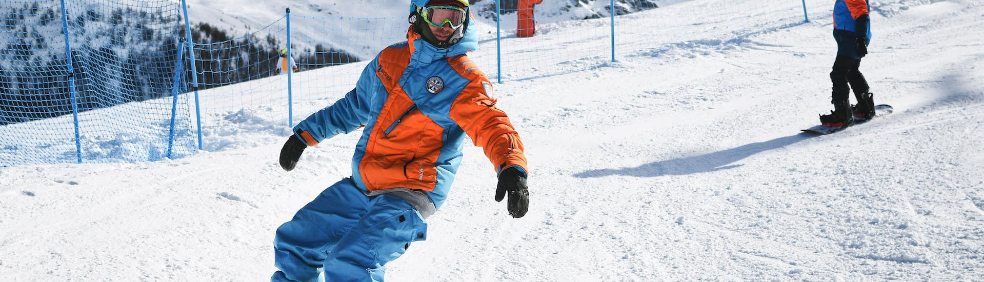 A snowboarder is following his instructor from the ski school YES Academy Sestriere during his Private Snowboarding Lessons for Kids & Adults - Special.