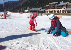A young snowboarder is learning the basics under the watchful eyes of her snowboard instructor from the ski school Moonshot La Bresse during her Private Snowboarding Lessons (from 6 years) - Low Season.