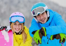 An instructor from the ski school Skischule Kahler Asten with his smiling pupil during Private Snowboarding Lessons (from 9 years) for All Levels.